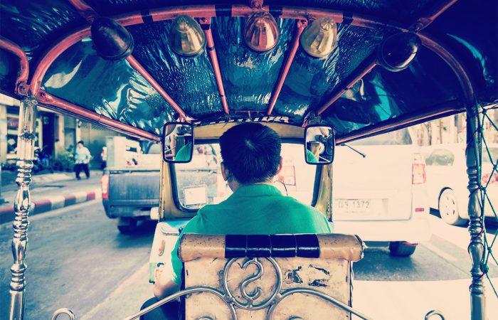 An auto rickshaw driving through the streets of Thailand