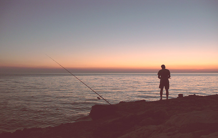 A man fishing off the rocks at sunset