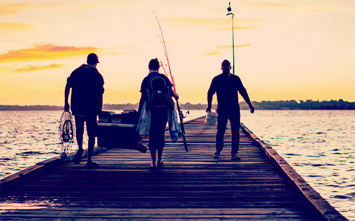 3 men catching fish off a jetty in Perth, Western Australia